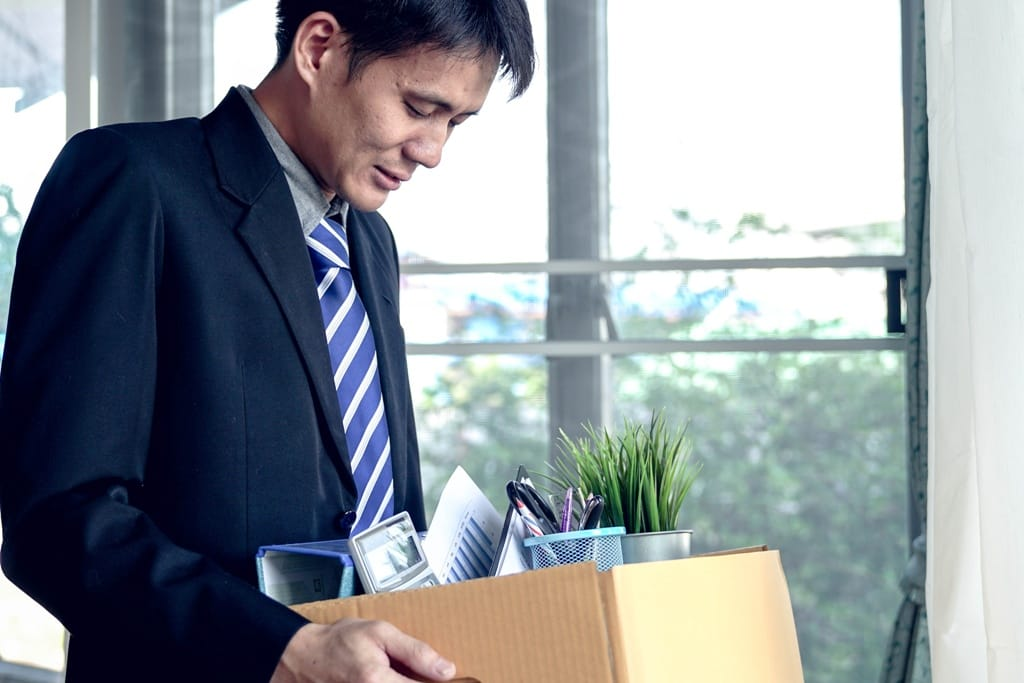 man holding a box of items leaving his job